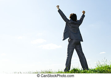 Back of happy businessman standing with raised arms on green grass on the background of azure sky