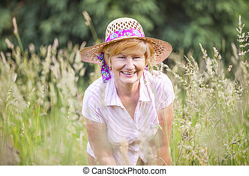 Positivity. Happy Senior Peasant Woman in Meadow smiling. Mature Friendly Lady in Bonnet