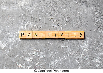 positivity word written on wood block. positivity text on cement table for your desing, concept