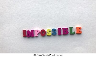 possible. coloured wooden letters on a white sheet of paper.