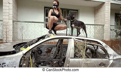 Post apocalypse. A girl is standing in a car and holding a dog on a leash.