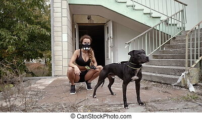 Post apocalypse. Athletic girl in a hypoxic mask holds a dog on a leash.