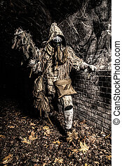 Post apocalyptic creature in gas mask armed gun