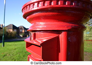Traditional red British post box on a street corner