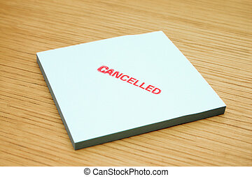 Post-it note. - Post-it note stamped cancelled on the wooden...