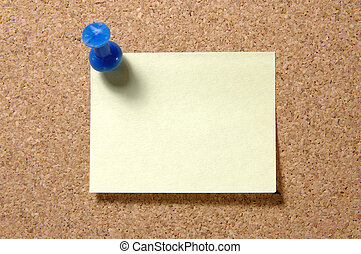 Post-it note with pushpin on corkboard - Yellow post-it note...