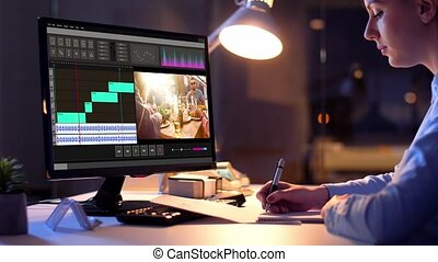 editor working on video file on computer at night - post...