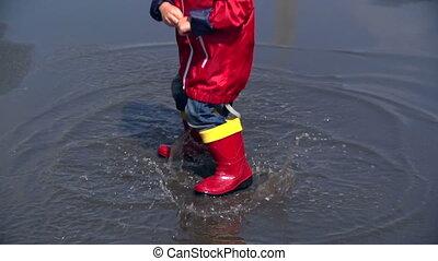 Post-Rain Adventure - Unrecognizable child splashing water...