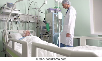 Post-Surgery Patient - Young nurse comparing indices in the...