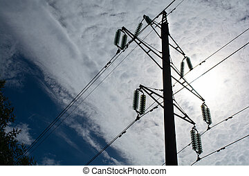 post with wires early in the morning against the sky