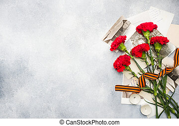 Postcard may 9 - red carnations Ribbon George Old photos on a concrete background. Symbol of victory in the great Patriotic war