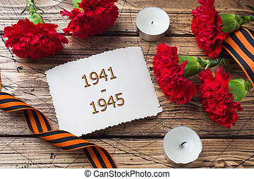 Postcard may 9 - red carnations Ribbon George Old photos on a wooden background. Symbol of victory in the great Patriotic war