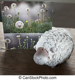 Postcard of a lamb in a meadow with dandelions.