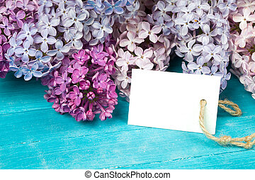 Postcard with splendid lilac flowers and empty tag for your text on aged wooden background.