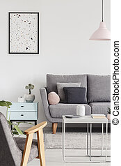 Poster above cabinet next to grey couch in living room interior with armchair and lamp. Real photo