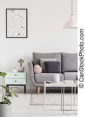 Poster above cabinet with plant next to grey couch in living room interior with lamp. Real photo