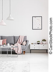 Poster above cupboard next to grey couch in white living room interior with lamps. Real photo