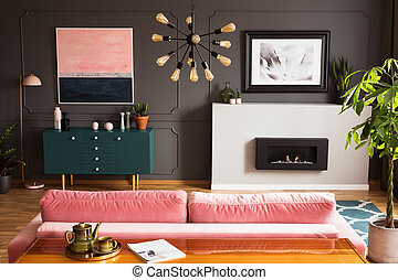 Poster above fireplace in grey living room interior with plant next to pink sofa and table. Real photo