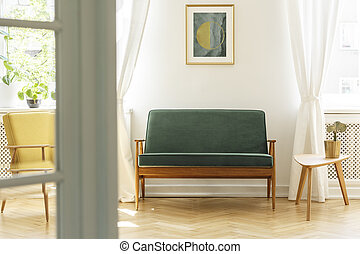 Poster above green wooden sofa in vintage living room interior with white table. Real photo