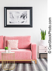 Poster above pink couch in modern living room interior with plant on gold table. Real photo