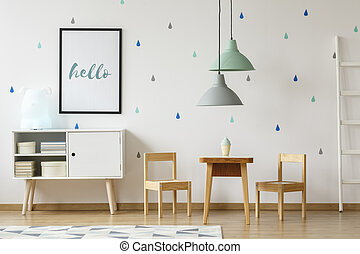 Poster above white cabinet next to wooden chairs and table in pastel kid's room interior. Real photo