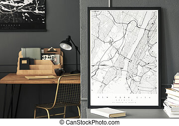 Poster and book on grey cabinet in workspace interior with gold chair at desk. Real photo