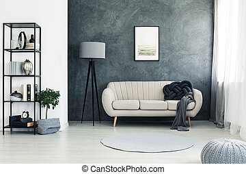 Poster on concrete wall above sofa with dark blanket next to lamp in bright living room with plant and pouf