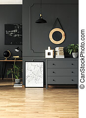 Poster next to grey cabinet with plant and books in living room interior with wooden floor. Real photo
