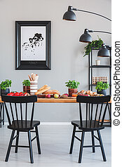 Poster on grey wall in industrial dining room interior with black chairs and lamp at table. Real photo