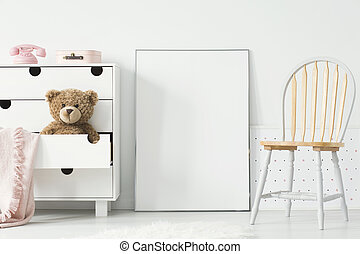 Poster with mockup between chair and cabinet with teddy bear in kid's room interior. Real photo