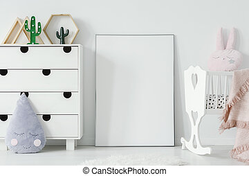 Poster with mockup between white cradle and cabinet in child's room interior. Real photo