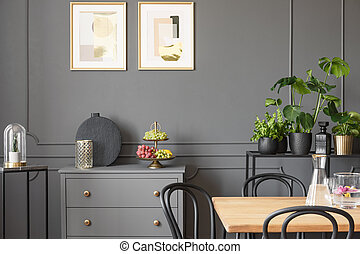 Posters above grey cabinet in dark dining room interior with plants and wooden table. Real photo