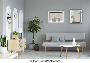 Posters above grey sofa in living room interior with plants next to wooden cupboard. Real photo