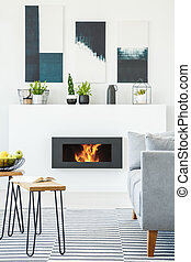 Posters and plants above fireplace in living room interior with table and grey couch. Real photo