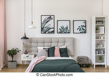 Posters in bright bedroom interior