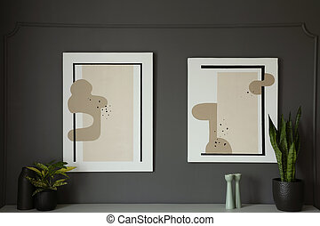 Posters on grey wall above cabinet with plants in living room interior. Real photo