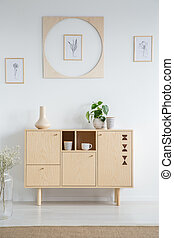 Posters on white wall above wooden cabinet in minimal living room interior with plants. Real photo