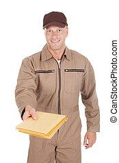 Portrait of mid adult postman giving envelopes over white background