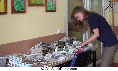 Postman woman sorting daily newspapers at work. 4K