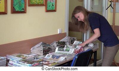 Postman woman sorting daily newspapers at work