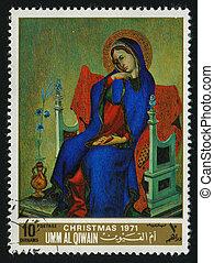 postmark - UMM AL QIWAIN - CIRCA 1971: woman sits in an...