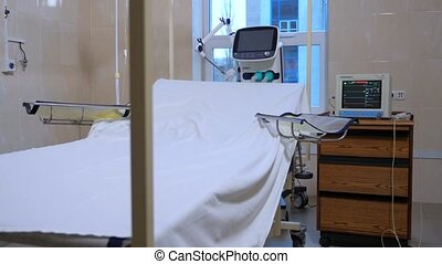 Fully-equipped postoperative ward in the hospital. Empty Hospital bed covered with white sheet. Preparation for surgery. Room for preparing a patient for surgery.