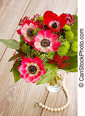 posy  of  red anemone flowers on wooden table