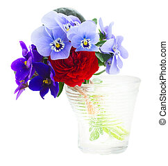 Posy of violets, pansies and ranunculus in glass isolated on...
