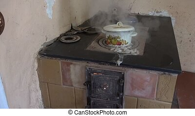 pot boiled and foam run out on clay stove in country kitchen. 4K