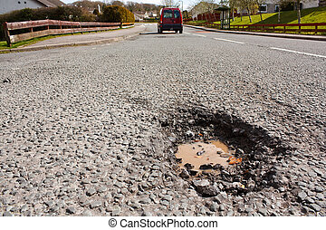 Pot hole in residential road surface - Large deep pothole an...