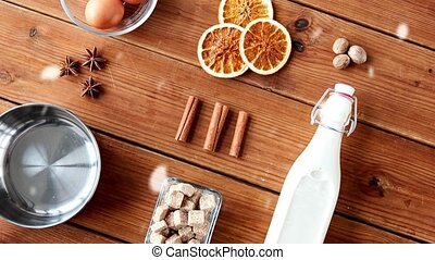 christmas and seasonal drinks concept - snow falling over pot, ingredients and aromatic spices for eggnog making on wooden background