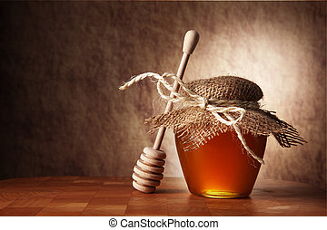 Pot of honey and wooden stick are on a table.