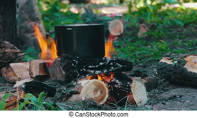 Pot on the Fire in Forest - Cooking food over a campfire at...