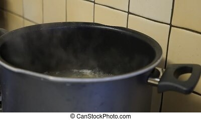 Pot on the stove with boiling water shot clip